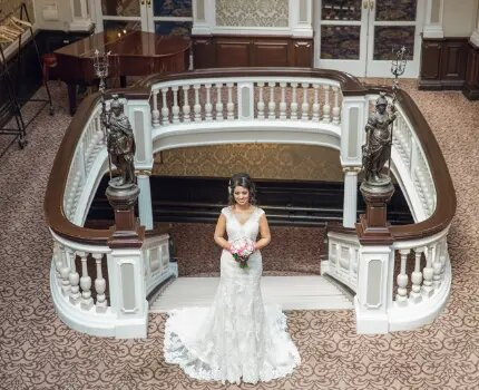 bride stading in front of staircase during wedding film shoot